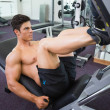 Male weightlifter doing leg presses in gym — Stock Photo #50057229