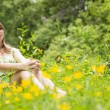 Cute young woman relaxing in field — Stock Photo #50057517