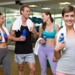 Fit woman smiling at camera in busy fitness studio — Stock Photo #50057565