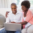 Couple relaxing on the couch with laptop — Stock Photo #50057699