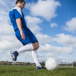 Football player in blue kicking the ball on pitch — Stock Photo