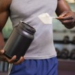 Body builder holding a scoop of protein mix in gym — Stock Photo #50058613