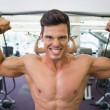 Shirtless muscular man using resistance band in gym — Stock Photo #50059715