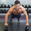 Muscular man doing push ups with kettle bells in gym — Stock Photo #50059733