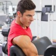 Muscular man exercising with dumbbell in gym — Stock Photo #50059743