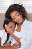 Pretty mother sitting on the couch with her sleeping daughter  — Stock Photo