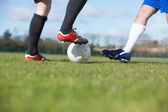 Football players tackling for the ball on pitch — Stock Photo