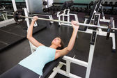 Fit brunette lifting heavy barbell lying on bench — Stock Photo