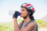 Fit woman going for bike ride drinking water  — Stock Photo