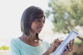 Pretty woman sitting outside using tablet pc — Stock Photo