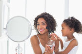 Pretty mother teaching her daughter about makeup  — Stock Photo