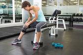 Fit brunette sitting on bench holding injured knee — Stock Photo