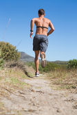 Shirtless man joggen met hartslagmeter rond borst — Stockfoto