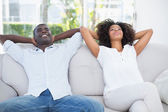 Attractive couple relaxing on couch together  — Stock Photo