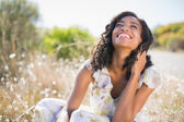 Happy pretty woman sitting on the grass in floral dress — Stock Photo