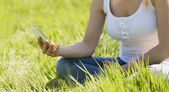 Pretty blonde sitting on grass sending a text — Stock Photo