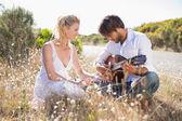 Man serenading girlfriend with guitar — Stock Photo