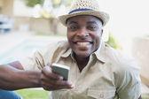 Uomo sorridente rilassante nel suo giardino sms sul cellulare — Foto Stock