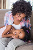 Cute daughter lying across mothers lap — Stock fotografie