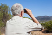 Hiker taking a break on country trail looking through binoculars — Stock Photo