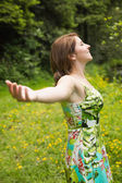 Woman with arms outstretched in field — ストック写真