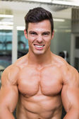 Smiling shirtless muscular man in gym — Foto de Stock