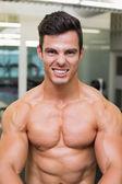 Smiling shirtless muscular man in gym — Stock Photo