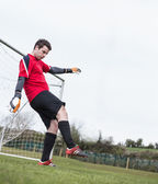 Goalkeeper in red kicking ball away from goal — Stock Photo