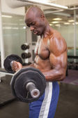 Muscular man lifting barbell in gym — Foto de Stock