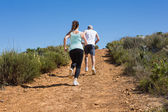 Fit couple running up mountain trail — Stock Photo
