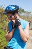 Fit cyclist fixing strap on helmet — Stock Photo