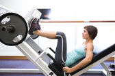 Fit brunette using weights machine for legs — Stock Photo