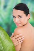Beautiful nude brunette posing with green leaves — Foto de Stock