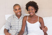 Happy couple sitting on bed smiling at camera — Stockfoto