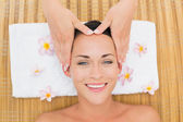 Smiling brunette enjoying a head massage — Foto Stock