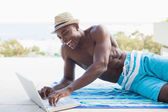 Handsome shirtless man using laptop poolside — Stock Photo