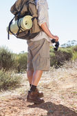 Hiker holding his binoculars on country trail — Photo