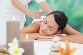 Brunette enjoying herbal compress massage — Stock Photo
