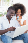 Attractive couple using laptop together on sofa to shop online — Stock Photo