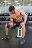 Muscular man exercising with dumbbell in gym — Photo