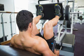 Male weightlifter doing leg presses in gym — Stock Photo