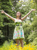 Woman with arms outstretched in field against trees — Stock fotografie