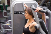 Athletic brunette using weights machine for arms — Stock Photo
