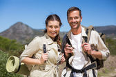Hiking couple standing and smiling at camera on country terrain — Stock Photo