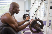 Muscular man lifting barbell in gym — Stock Photo