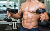 Mid section of shirtless muscular man exercising with dumbbells — Stock Photo