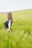 Pretty blonde in sundress standing in wheat field — Стоковое фото