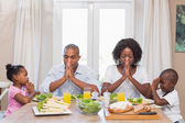 Happy family saying grace before meal — Foto Stock