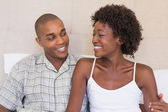 Happy couple sitting on bed smiling at each other — Stockfoto