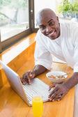 Happy man in bathrobe using laptop at breakfast — Stock Photo